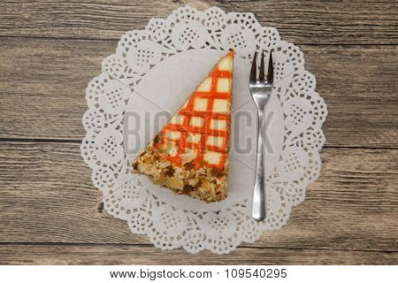 Fresh tasty sweet piece of  carrot cake on a white lace napkin and a dessert fork on a wooden background.