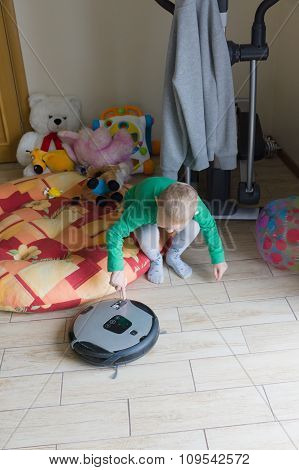 The Boy Watches The Robot The Vacuum Cleaner