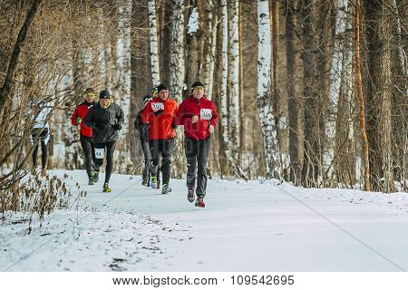General plan of running on a snowy road in forest group men athletes