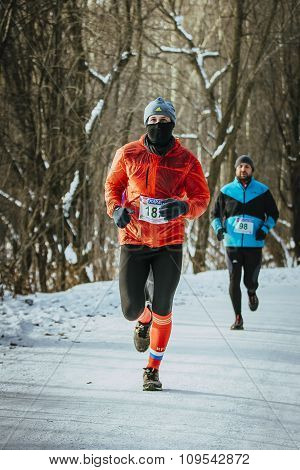male athlete running down a snowy alley in forest