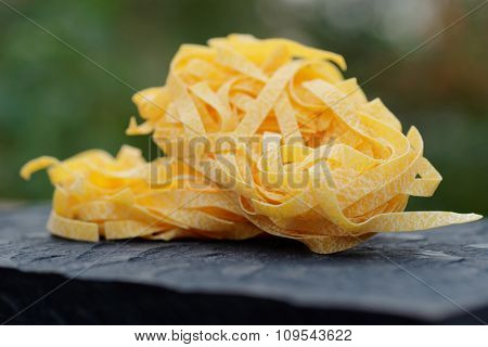 Egg tagliatelle on wooden plank, outdoor shot