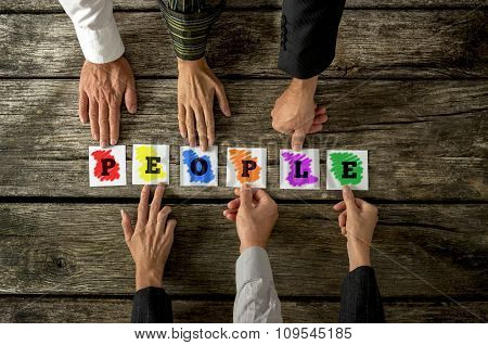 Top View Of Six People Assembling Colourful Word People