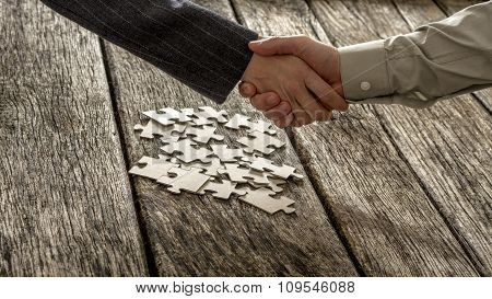 Closeup Of Male And Female Business Partners Shaking Hands Over A Pile Of Puzzle Pieces
