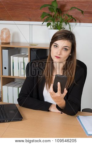 Portrait Of A Young Worried Business Woman Looking At Her Mobile Phone