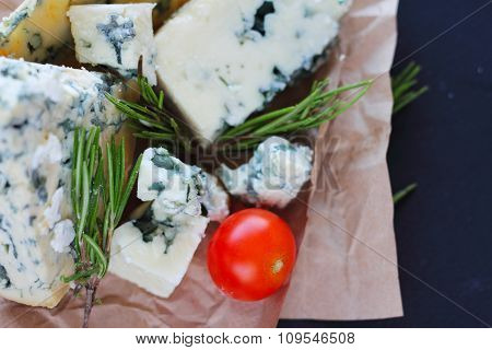 Roquefort cheese composition on dark background close up