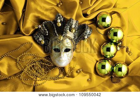 Background Of Golden Christmas Tree Balls With Gold Decorations And Golden Mask On Golden Shiny Silk