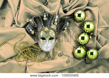 Background Of Christmas Tree Balls With Gold Decorations And Golden Mask On Shiny Silk Fabric Retro