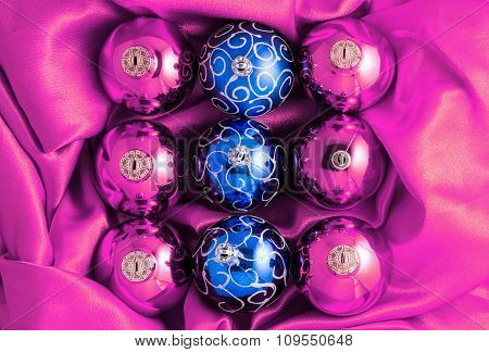 Background Of Pink And Blue Christmas Tree Balls On Pink Shiny Silk Fabric