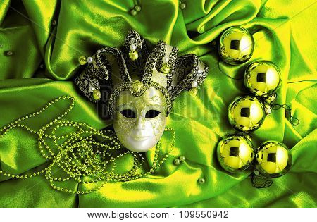 Background Of Golden Christmas Tree Balls With Gold Decorations And Golden Mask On Green Shiny Silk