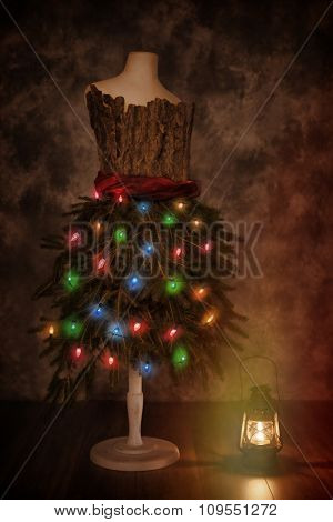 Vintage mannequin dressed for Christmas with old fashioned lamp