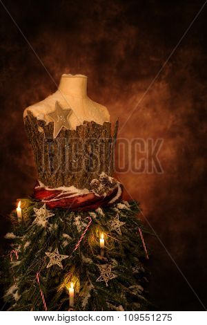 Close up of a vintage tailors mannequin dressed for Christmas with festive candles