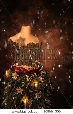 Close up of a vintage tailors mannequin dressed for Christmas with festive candles and falling snow