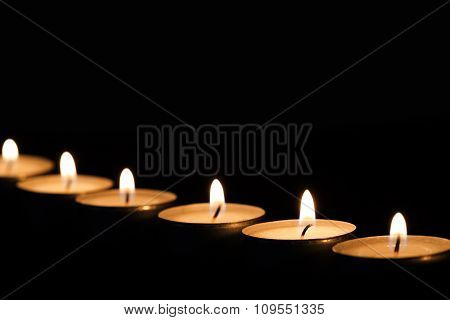 Burning tealights in darkness