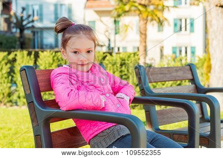 Little girl resting in the park on a nice sunny spring day, wearing bright pink jacket