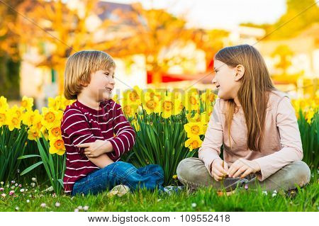 Two cute kids, little boy and his big sister, playing in the park between yellow daffodils flowers a