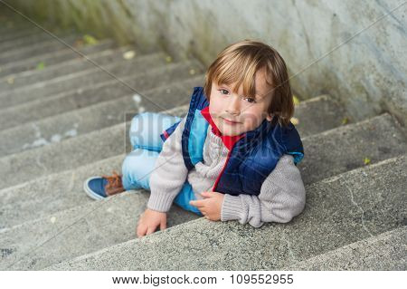 Fashion portrait of a cute little blond boy sitting on stairs in a city