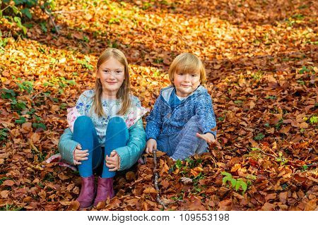 Autumn portrait of a cute girl and her little brother, playing in forest