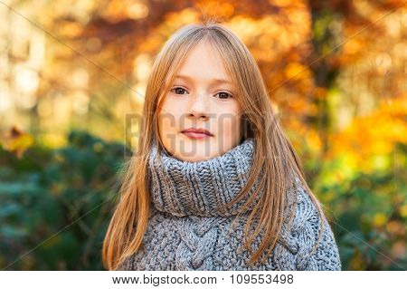 Outdoor portrait of a cute little girl in autumn forest, wearing grey knitted poncho