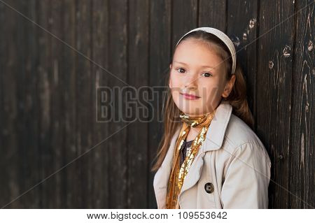 Outdoor portrait of a cute little girl wearing trench coat and golden scarf