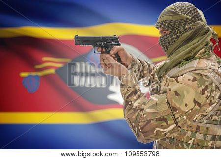 Male With Gun In Hand And National Flag On Background - Swaziland