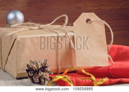 Gift Box Packed Brown Paper And Twine With Blank Tag Decorated Holiday Accessories On Wooden Table
