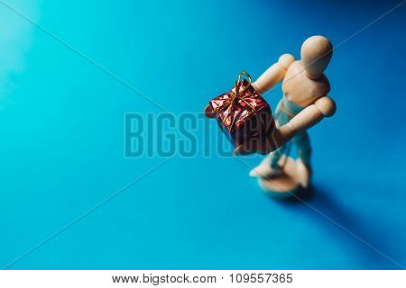 Wooden Hinged Mannequin With The Gift On The Blue Background