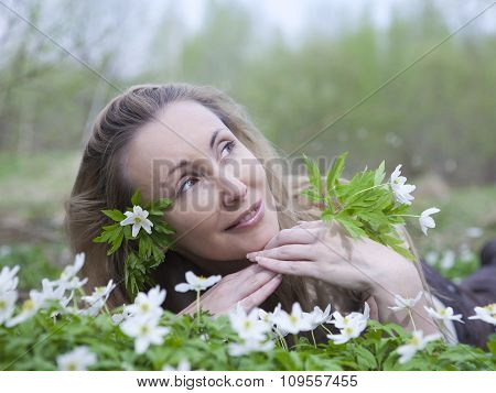 The young beautiful woman on a glade of blossoming snowdrops