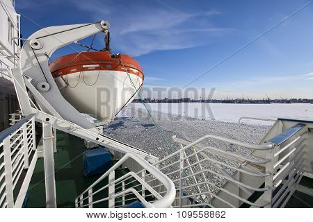 View from the Gulf of Finland covered with ice on St. Petersburg seaport and a lifeboat from a vesse