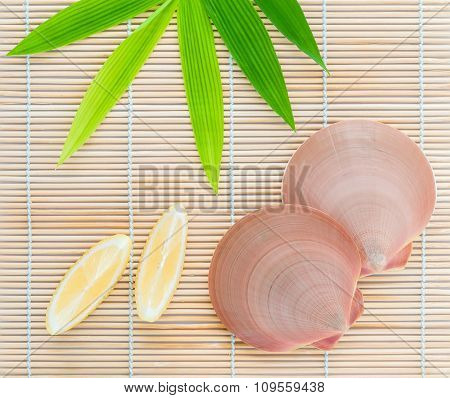 Raw Queen Scallops With Lemon Slice  On Bamboo Background And  Bamboo Leaves .