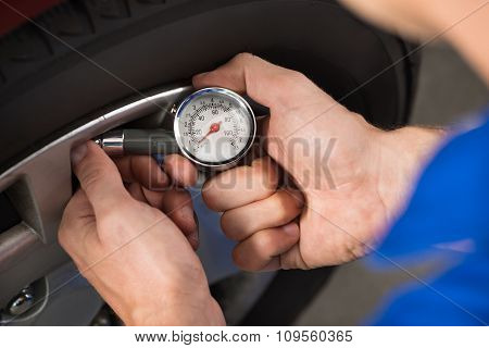Mechanic Checking Air Pressure Level In Car Tire