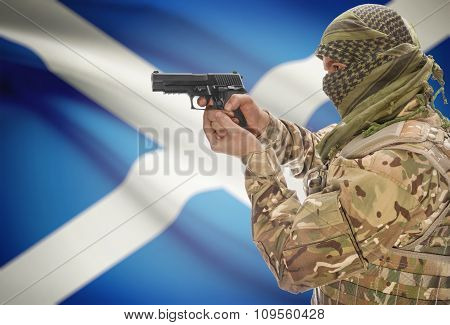 Male In Muslim Keffiyeh With Gun In Hand And National Flag On Background - Scotland