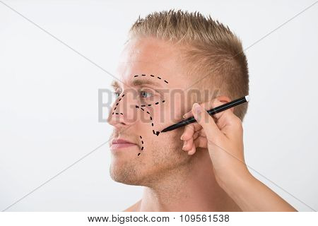 Person's Hand Drawing Correction Line With Pen Near Man's Eyes
