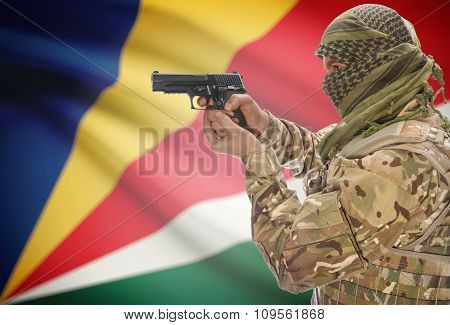 Male In Muslim Keffiyeh With Gun In Hand And National Flag On Background - Seychelles