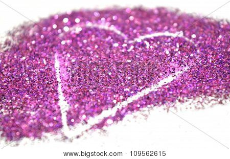 Blurry abstract background with heart of purple glitter sparkle on white surface