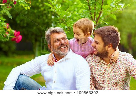 Portrait Of Happy Grandpa, Father And Son In Spring Garden