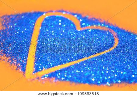 Blurry abstract background with heart of blue glitter sparkle on orange surface