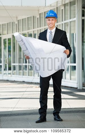 Smiling Engineer Holding Blue Print