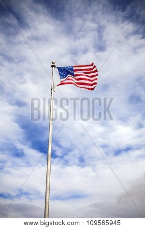 American Flag On Blue Cloudy Sky With Vignette Effect