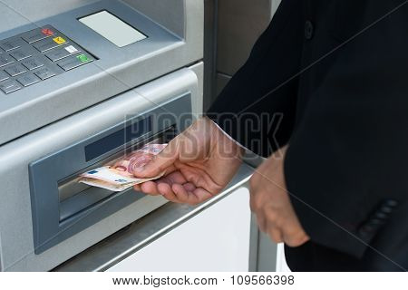 Person Withdrawing Money From Atm Machine
