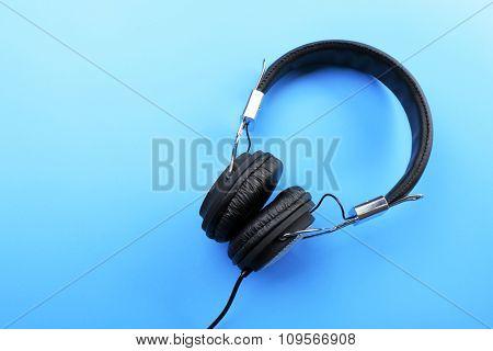 Black headphones on blue background