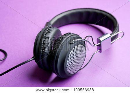 Black headphones on purple background