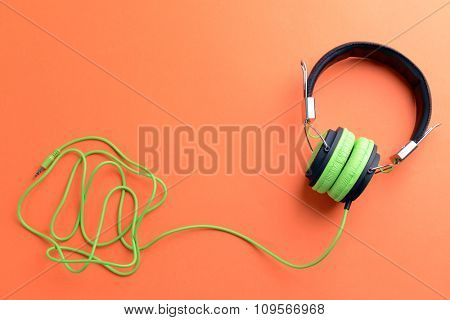A pair of green-black headphones, on orange background