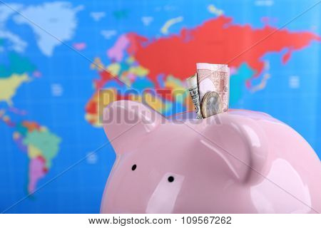 Piggy money box and banknotes on world map background, close-up