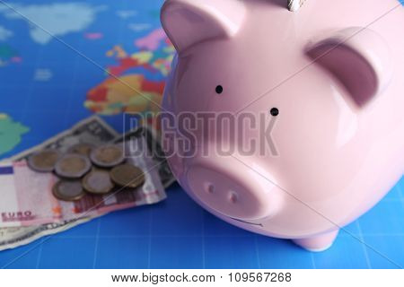 Piggy money box, banknotes and coins on world map background, close-up