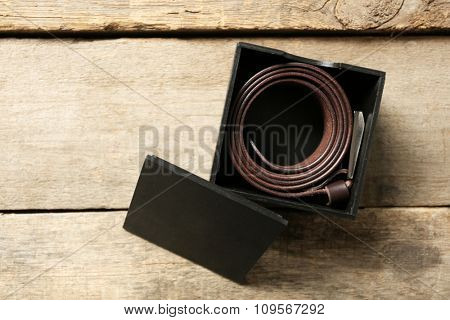 Leather belt with buckle in gift box on wooden background
