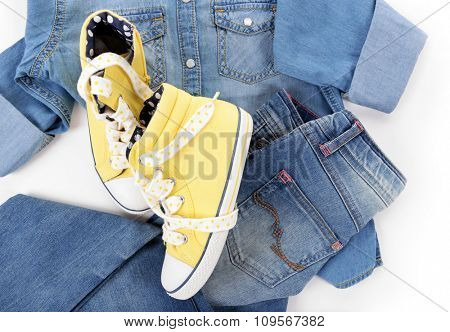 Blue denim shirt and jeans with yellow gym shoes on white background