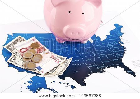 Piggy money box, banknotes and coins on the USA map background