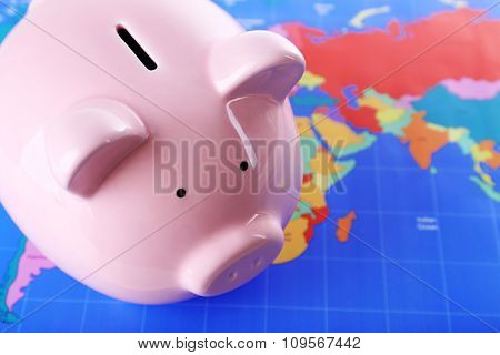 Piggy money box on world map background