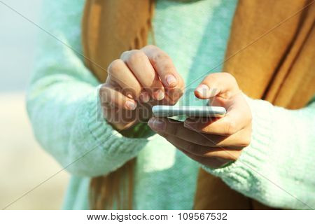 Female hands holding a mobile phone outdoors, on blurred background