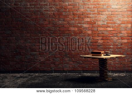 Small wooden table and books on red brick wall background
